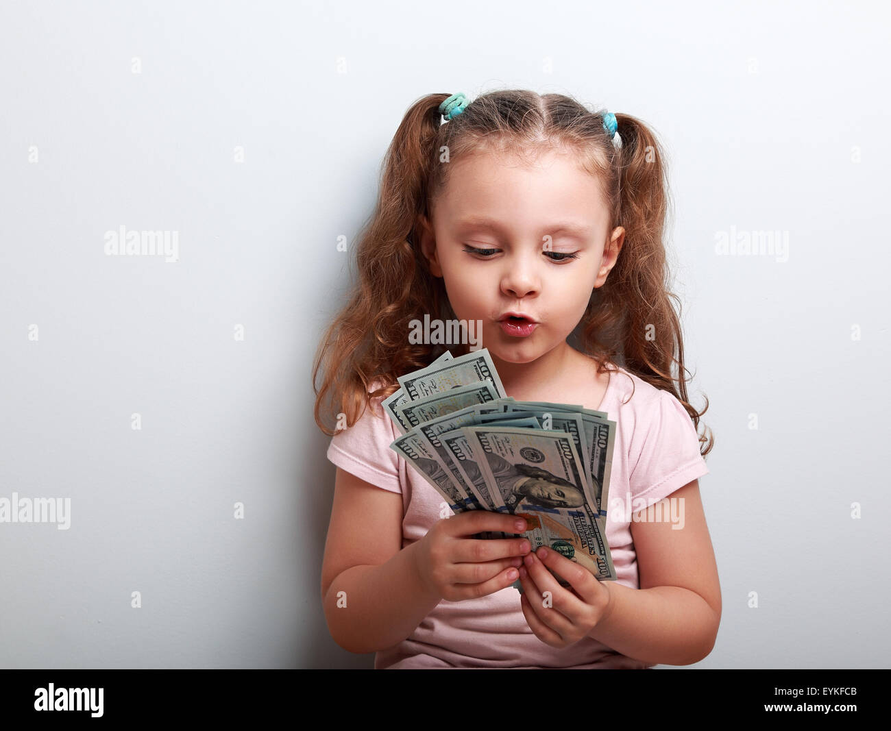 Fun grimacing kid girl looking and counting money in the hands on blue background - Stock Image