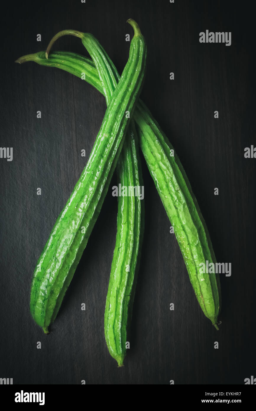 Angled Gourd or Angled Loofah Sponge gourd with Mystic Light on black wood background - Stock Image