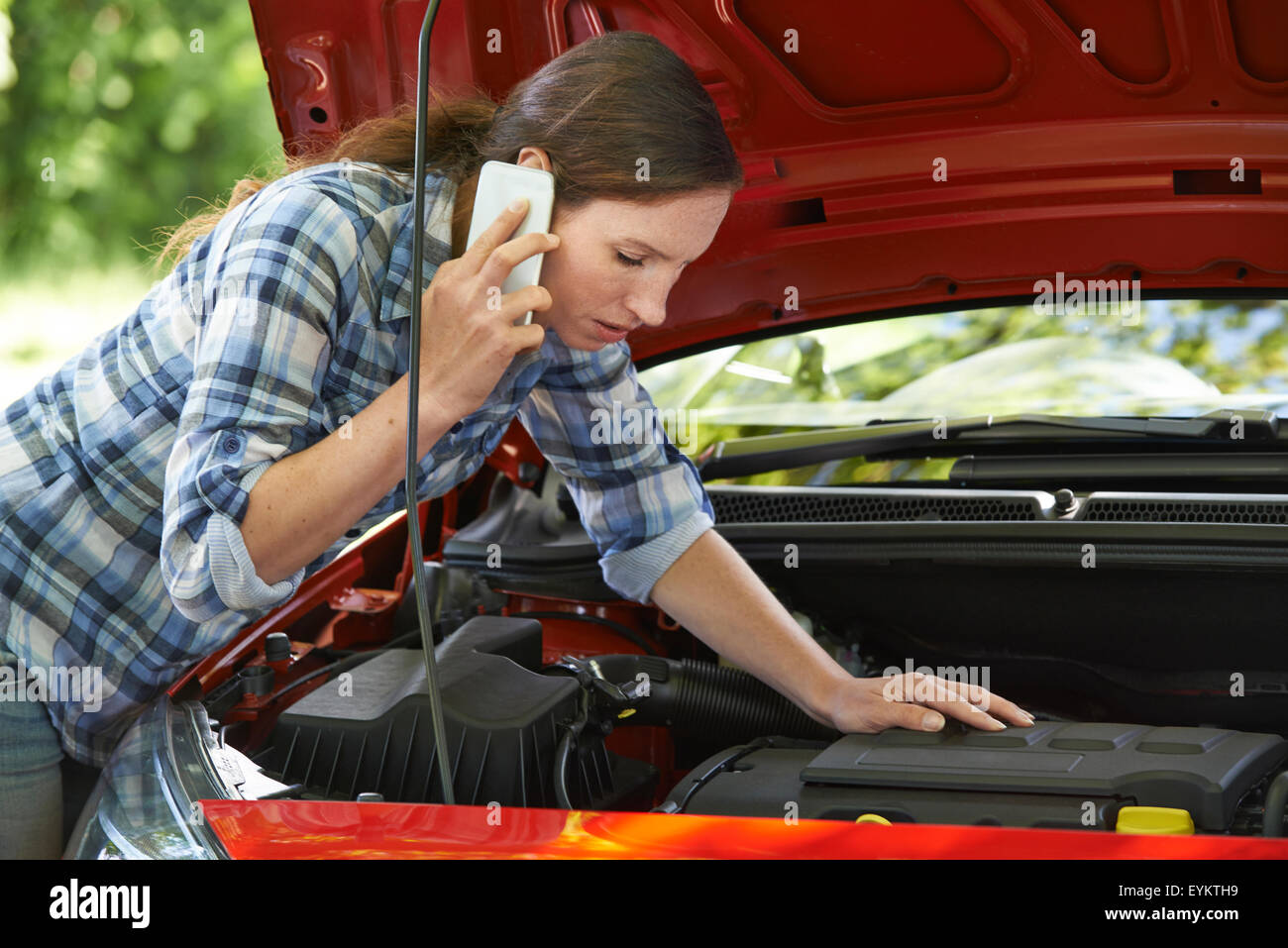 Female Motorist Phoning For Help After Breakdown - Stock Image
