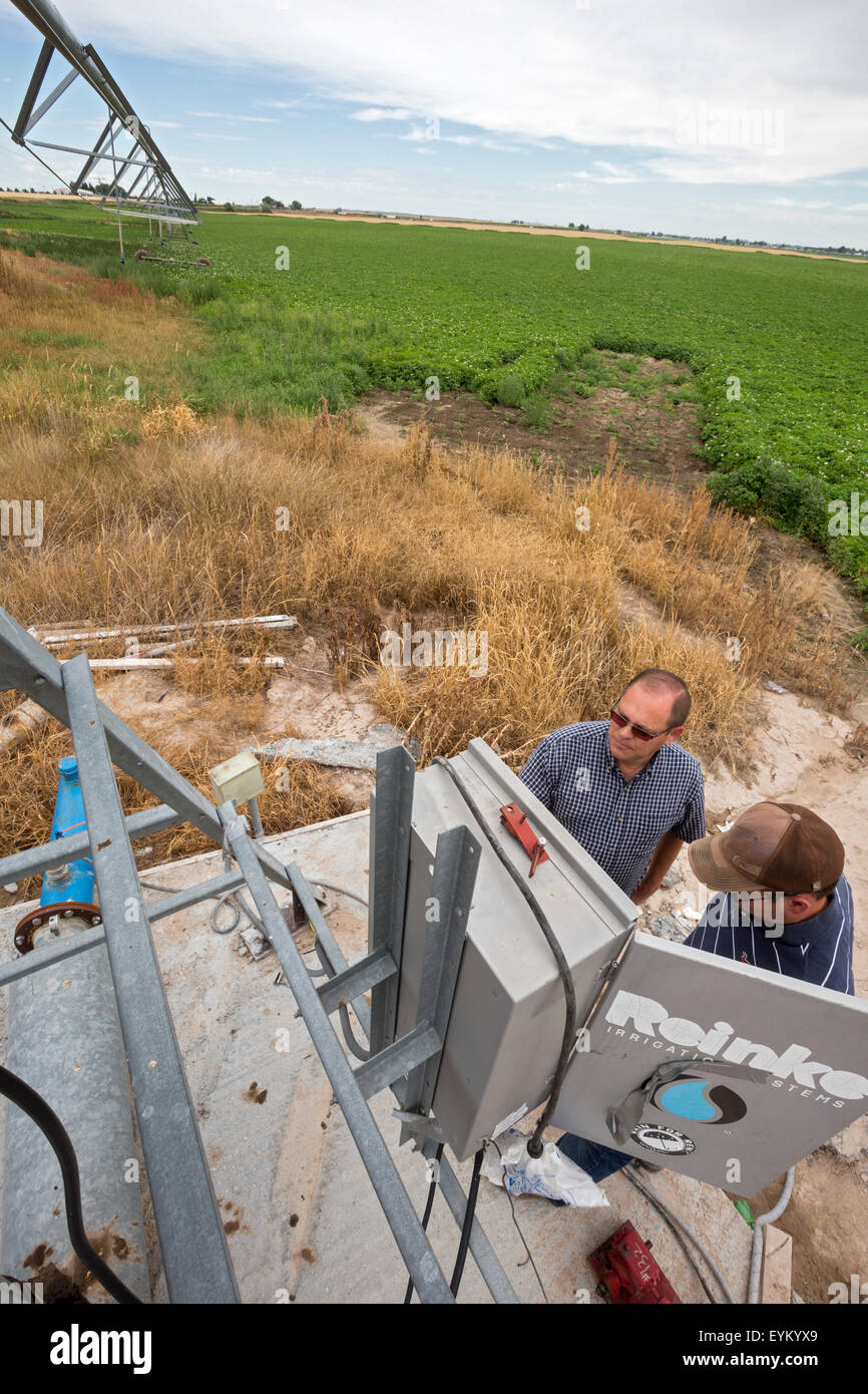 Shelley, Idaho - Idaho potato farmer Bryan Searle (left) and his son, Ray, adjust the controls for a center-pivot - Stock Image