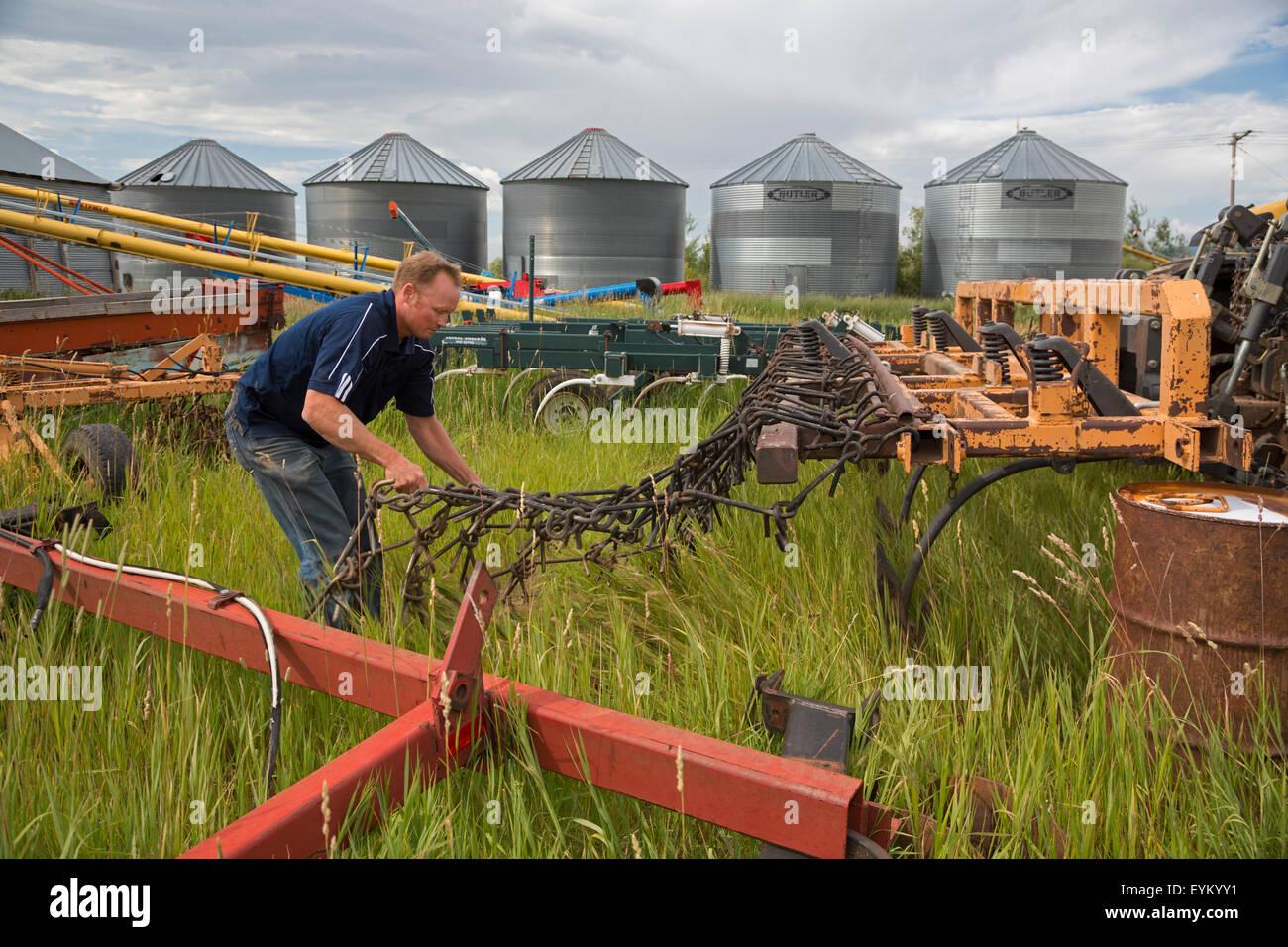 Driggs, Idaho - Wyatt Penfold handles equipment on his farm, where he grows seed potatoes. - Stock Image