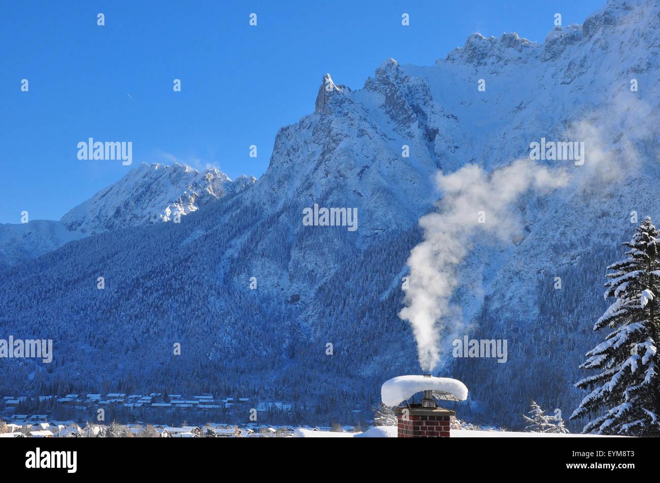 Deutschland, Bayern, Isartal, Mittenwald, Winterlandschaft, Schornstein, rauchend, Bergspitzen - Stock Image