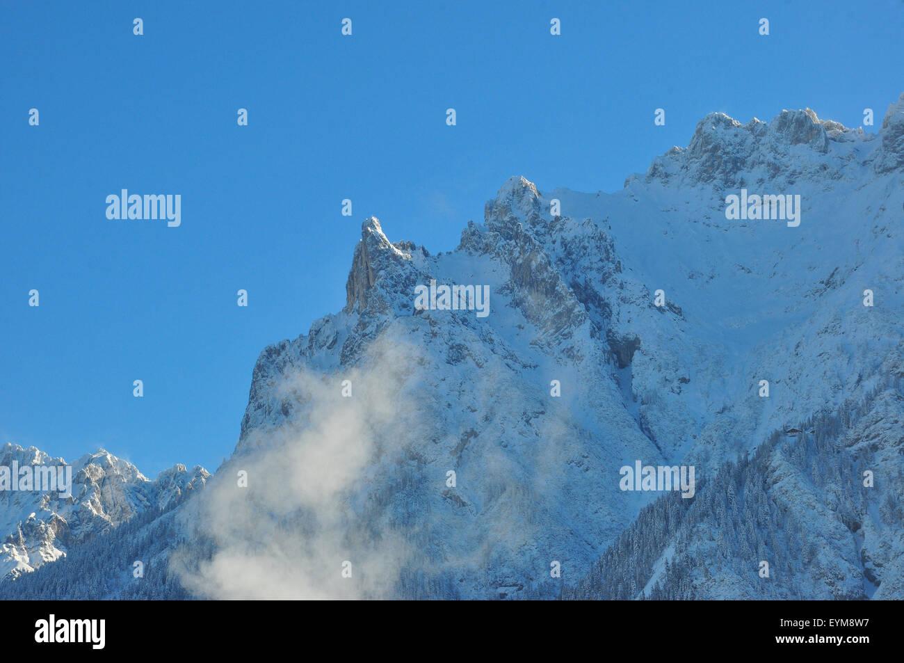 Deutschland, Bayern, Isartal, Winterlandschaft, Schornstein, rauchend, Bergspitzen - Stock Image