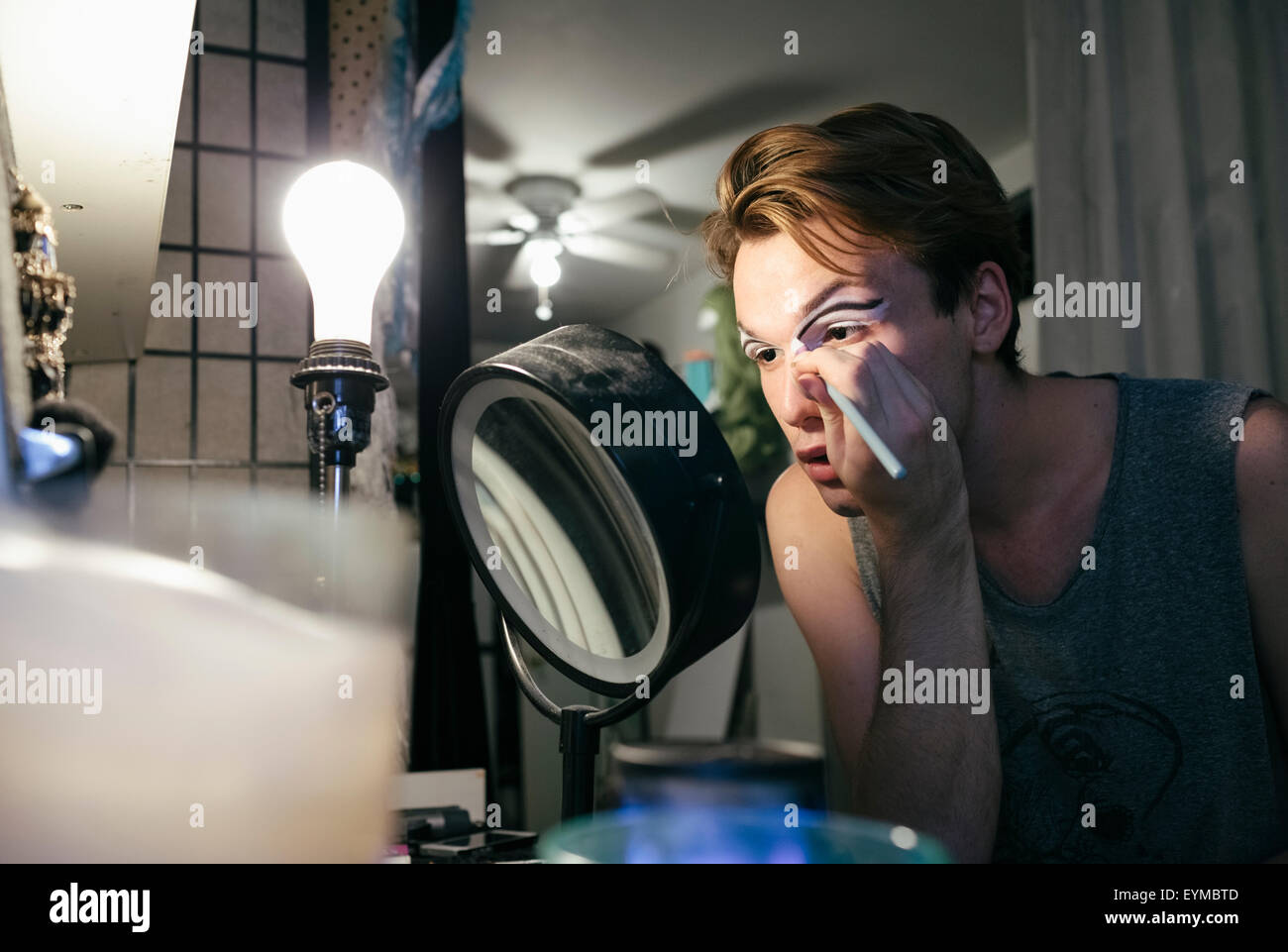 Male drag queen putting on make up and dressing up in preparation for a performance Stock Photo