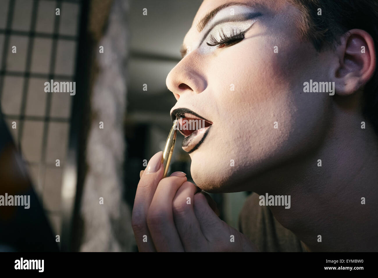 Male drag queen putting on make up and dressing up in preparation for a performance - Stock Image