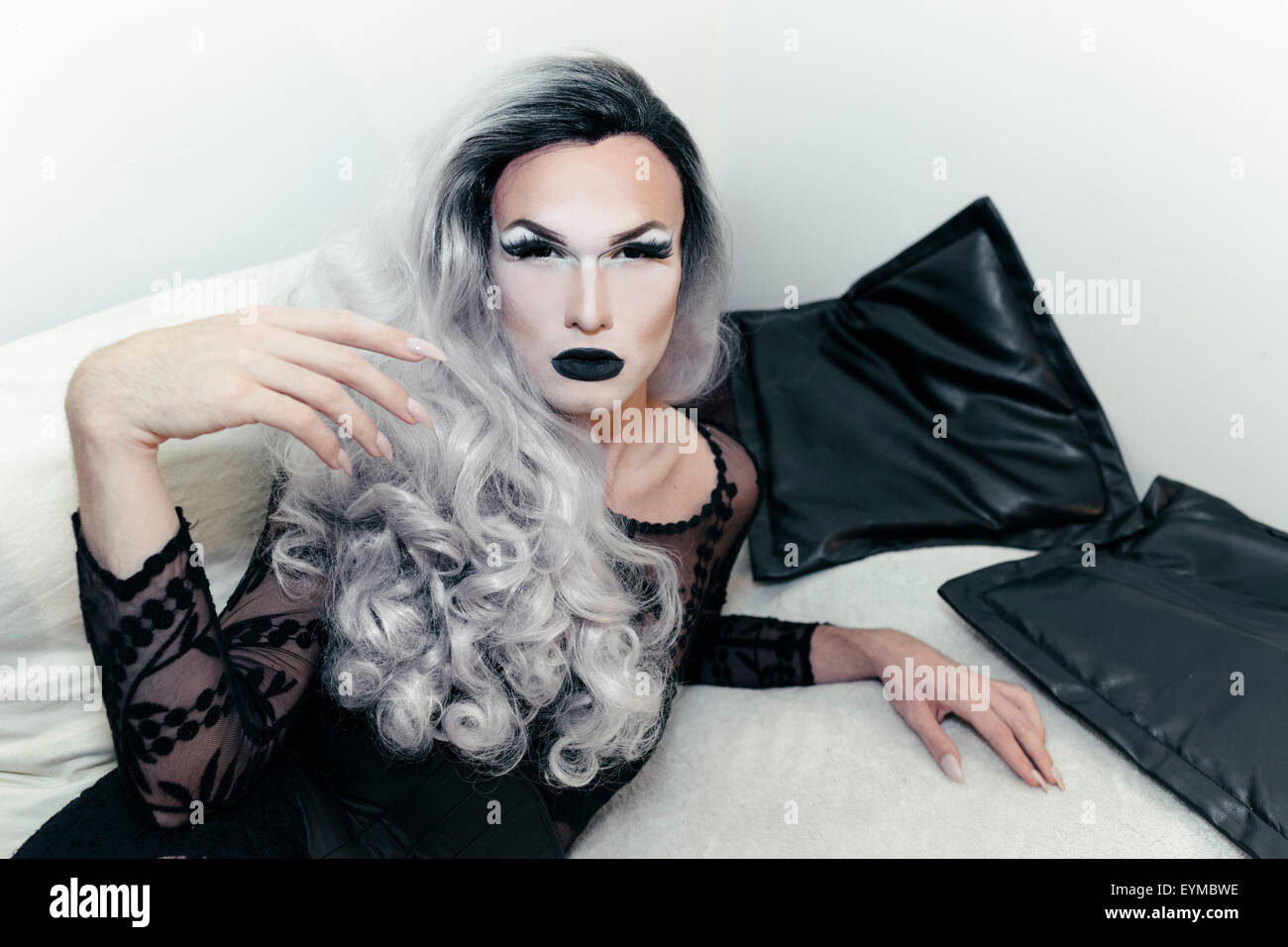 Male drag queen posing for pin-up style glamor portrait at home. Stock Photo