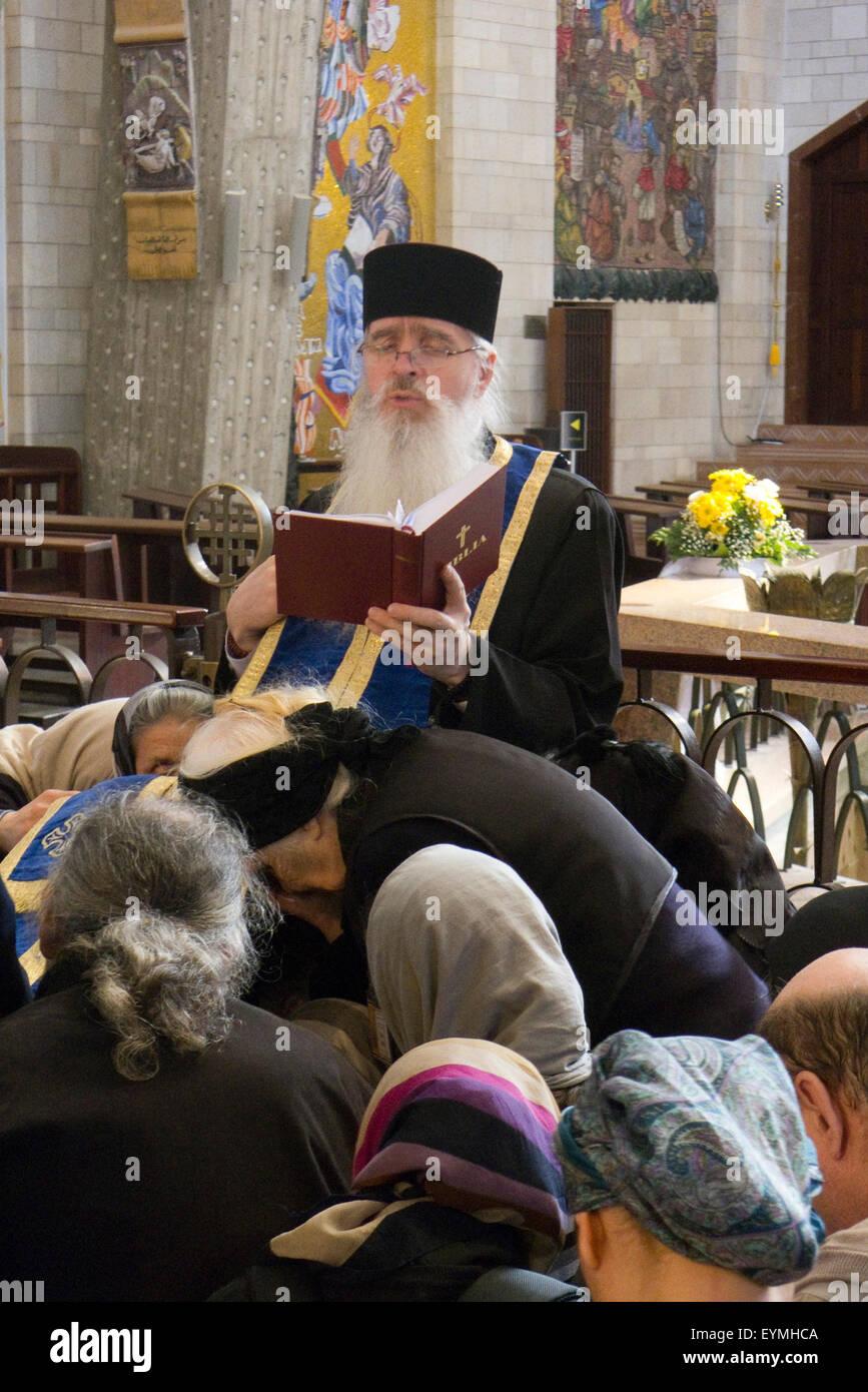 Annunciaton Church, inside, orthodox Christians while praying, Nazareth, Galilee, Israel - Stock Image