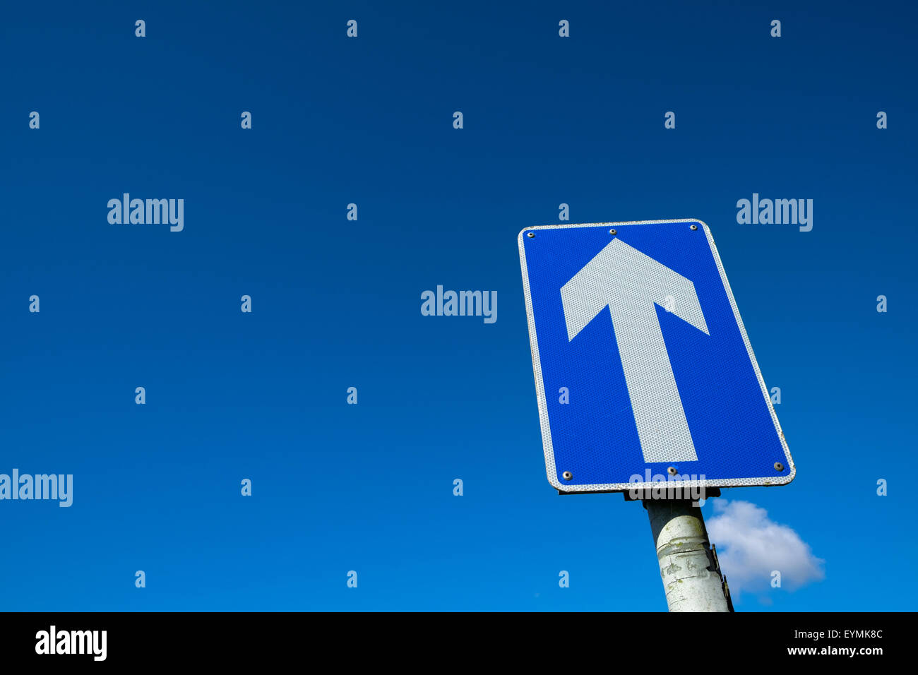 An arrow road sign against a blue sky with copy space UK - Stock Image