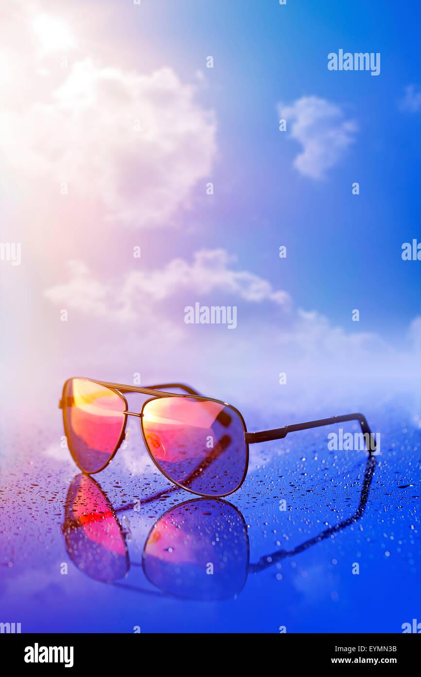 New sunglasses on wet reflective surface. - Stock Image