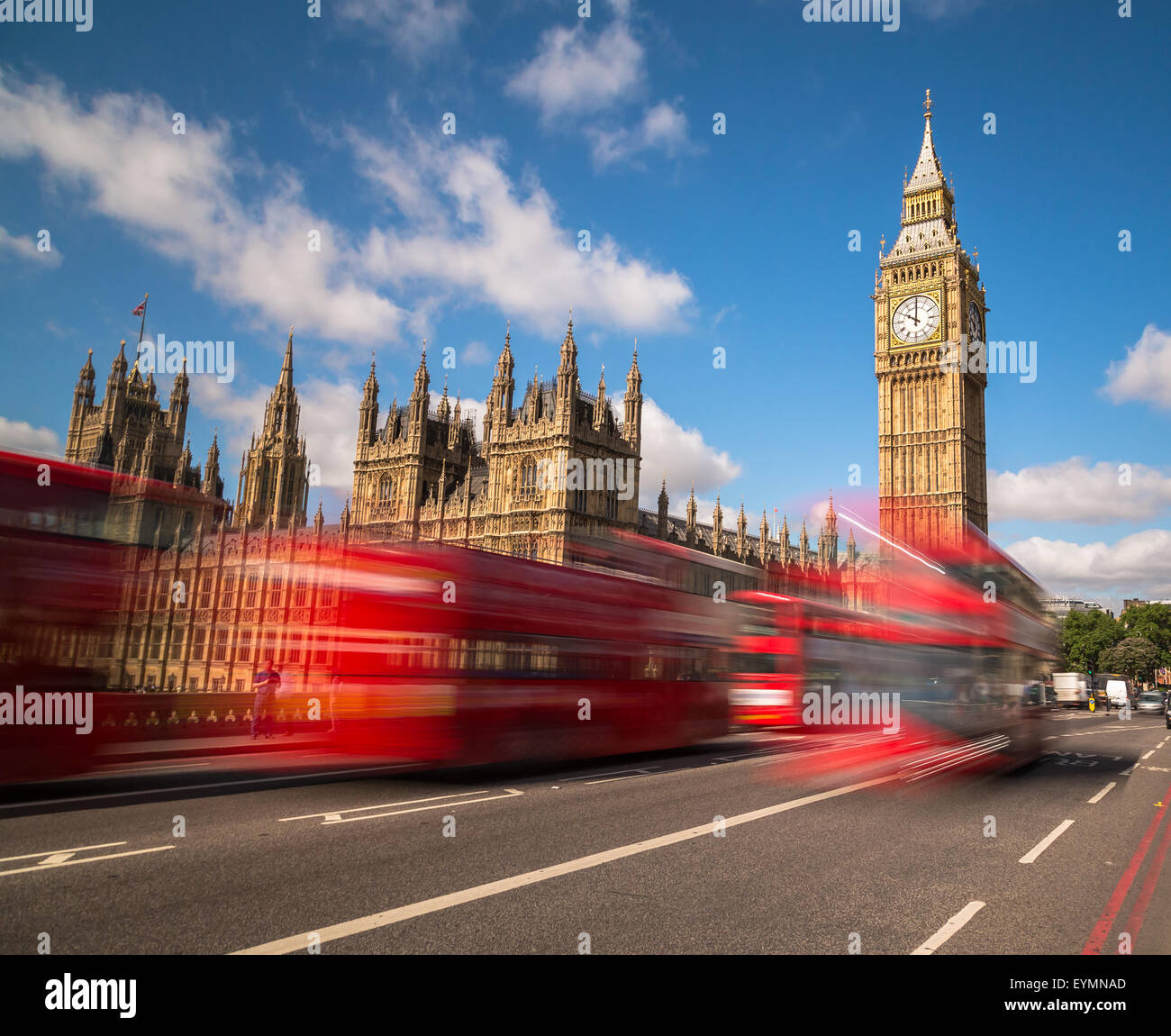 Big Ben in Westminster with red London Buses going past during the day. There is space for text in the image - Stock Image