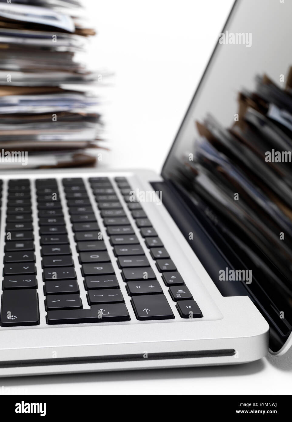 Laptop with a pile of files in background - Stock Image