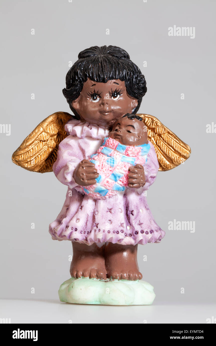dark-skinned Christmas angel with a baby, - Stock Image