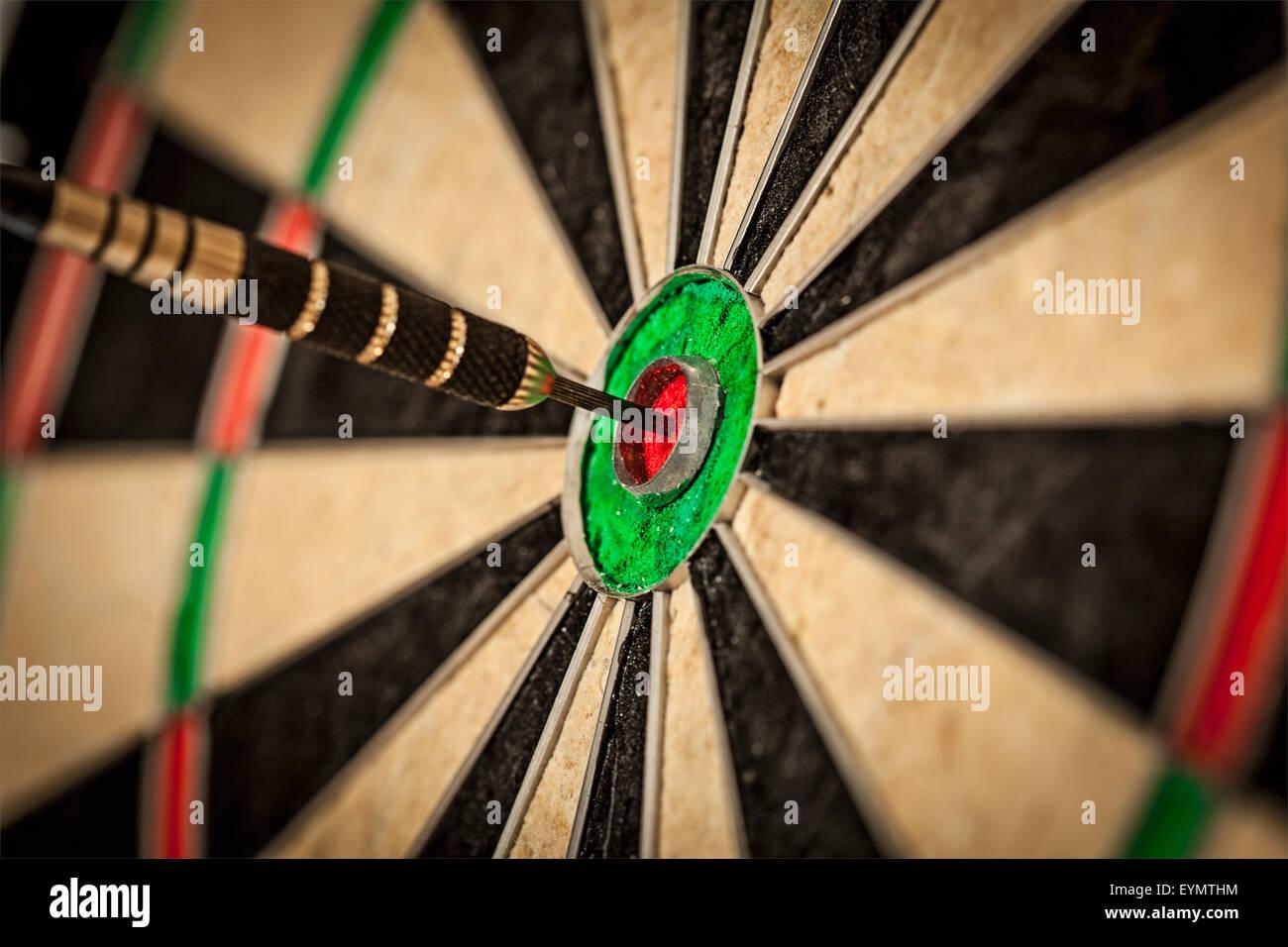 Success hitting target aim goal achievement concept background - dart in bull's eye close up Stock Photo