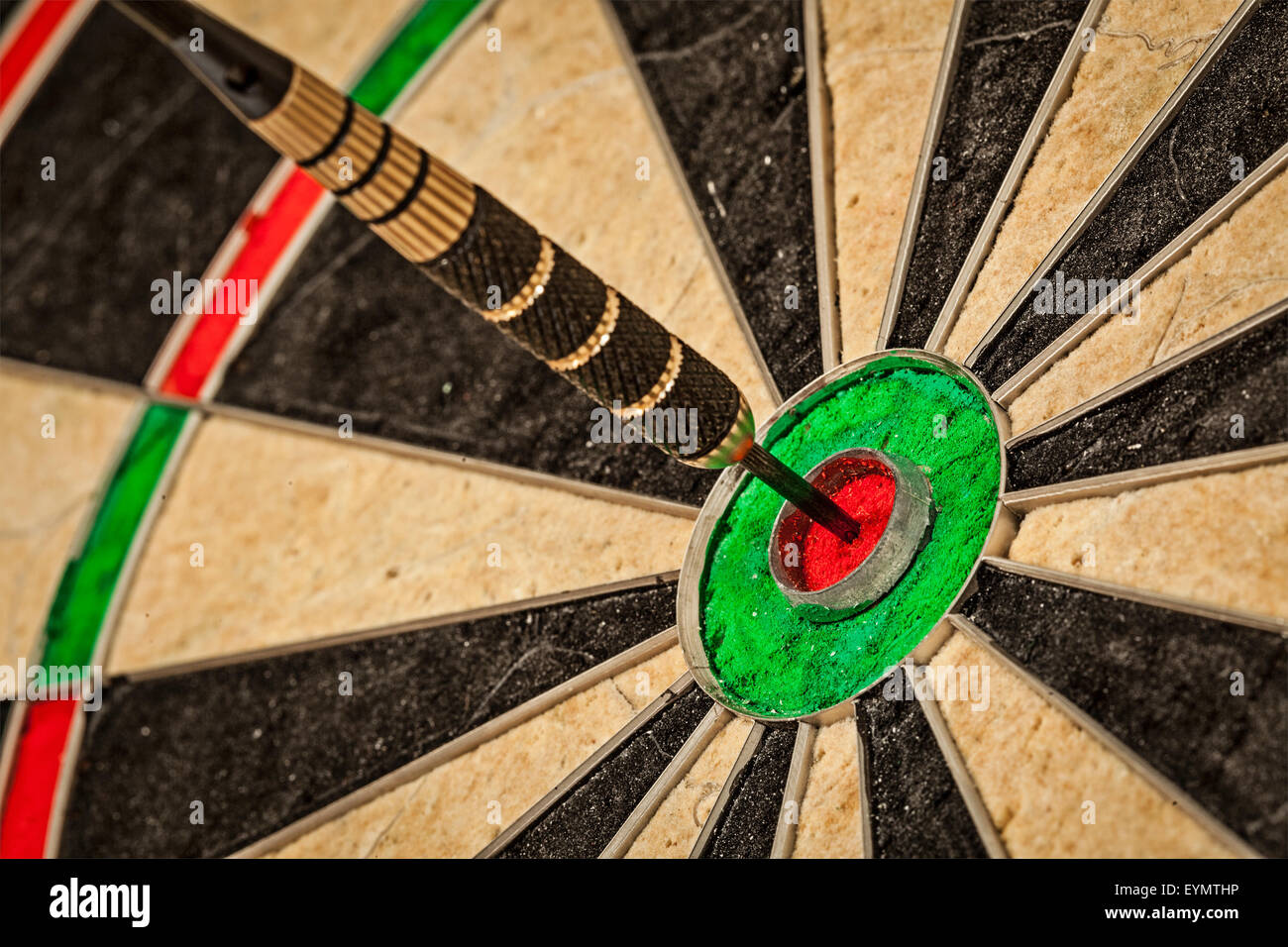 Success hitting target aim goal achievement concept background - dart in bull's eye close up - Stock Image