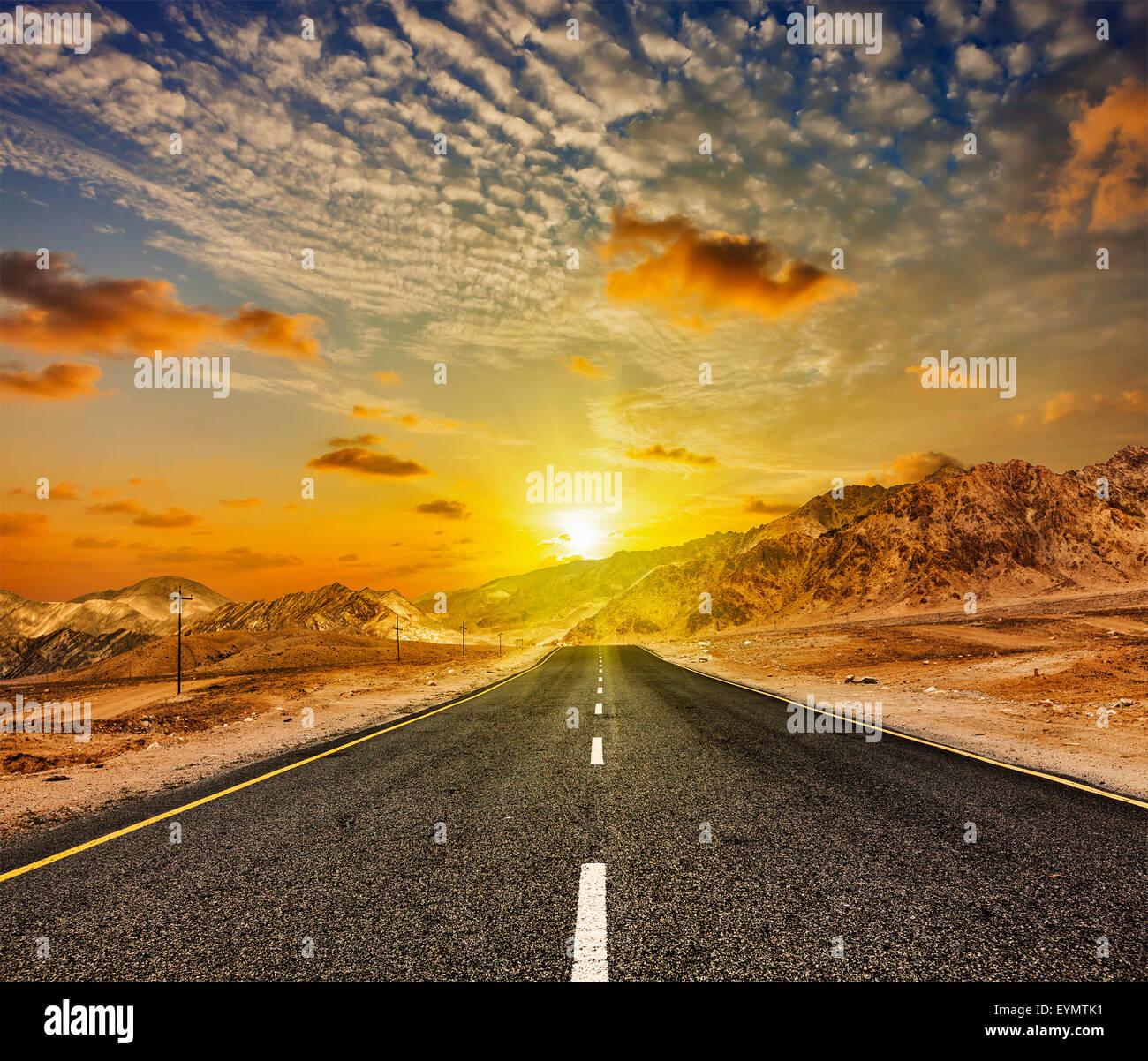 Travel forward concept background - road in Himalayas with mountains and dramatic clouds on sunset. Ladakh, Jammu - Stock Image