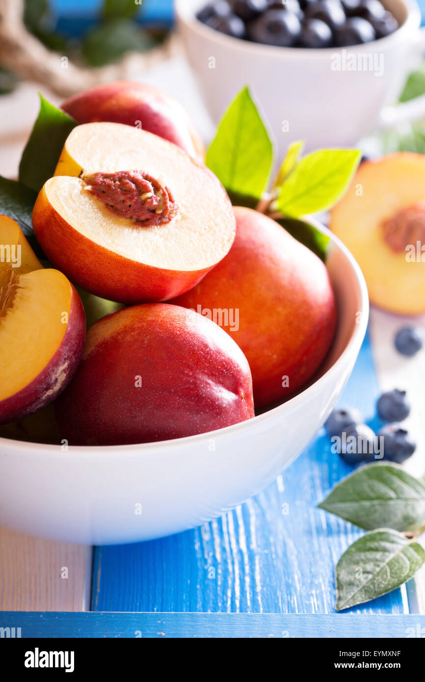 Fresh nectarines in a bowl with colorful background - Stock Image