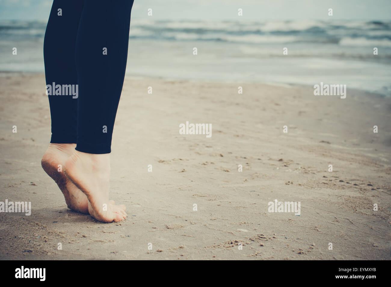 Girl's bare feet on wet sand - Stock Image
