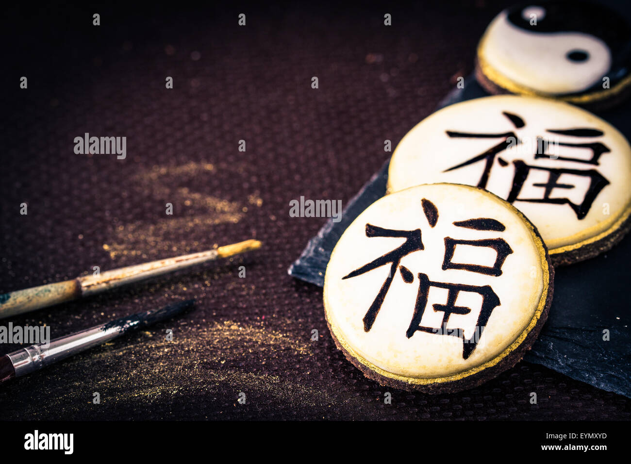 Hand-painted cookies with chinese characters 'fortune', bamboo and yin yang. Selective focus. - Stock Image
