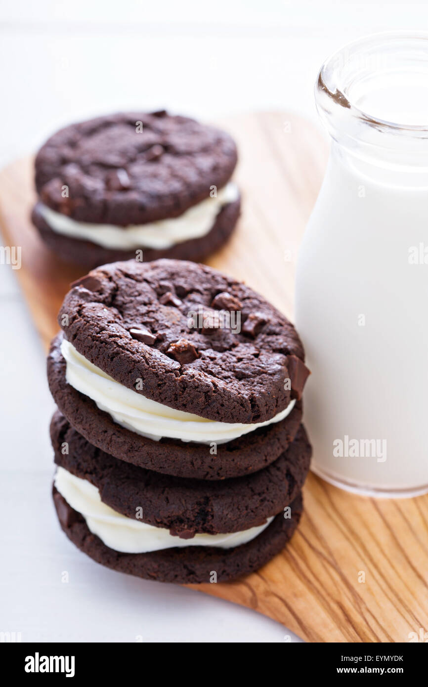 Chocolate brownie cookies with cream filling served with milk - Stock Image