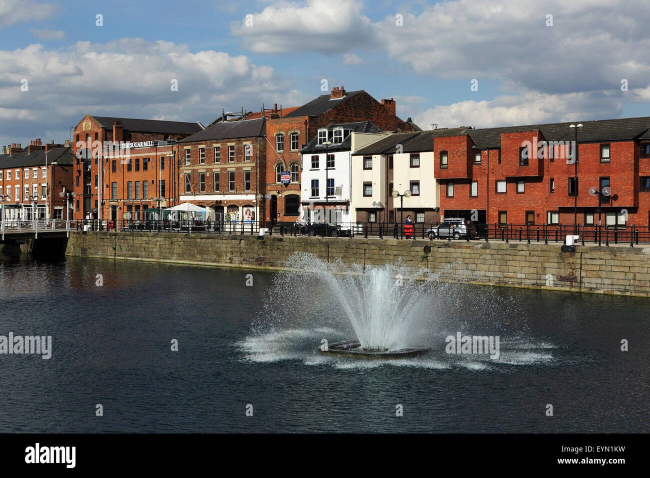 A fountain sprays water at Hull Marina in Hull, England. Former warehouses stand by the waterfront. - Stock Image