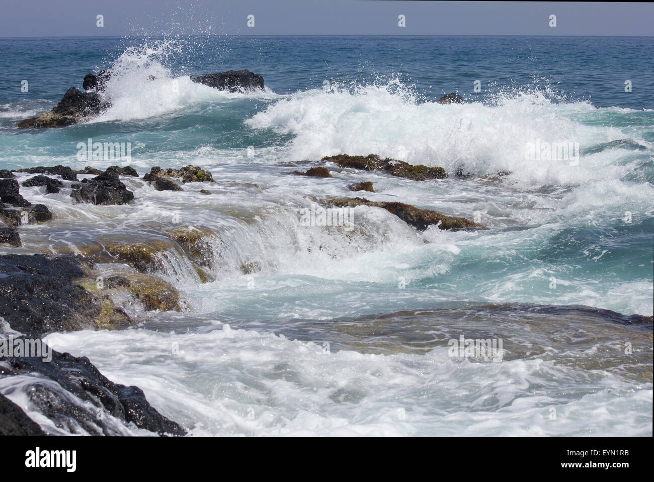 Waves crashing on rocks. White surf and blue sea and sky on a summer day. - Stock Image