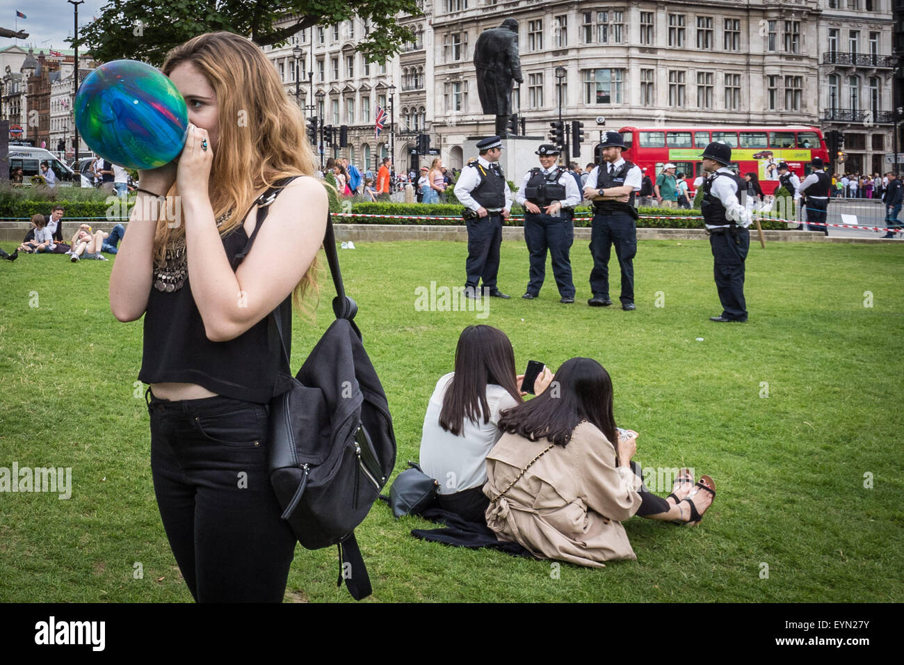 """London, UK. 1st August, 2015. Campaigners inhale balloons inflated with nitrous oxide, commonly known as """"laughing gas"""" to get high during a protest in Westminster's Parliament Square against a proposed bill that aims to make selling any psychoactive substance illegal. Credit: Guy Corbishley/Alamy Live News Stock Photo"""