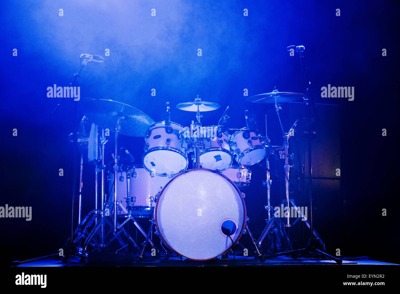 Full Rock Drum Kit On Stage With Blue Lighting And No Drummer Stock