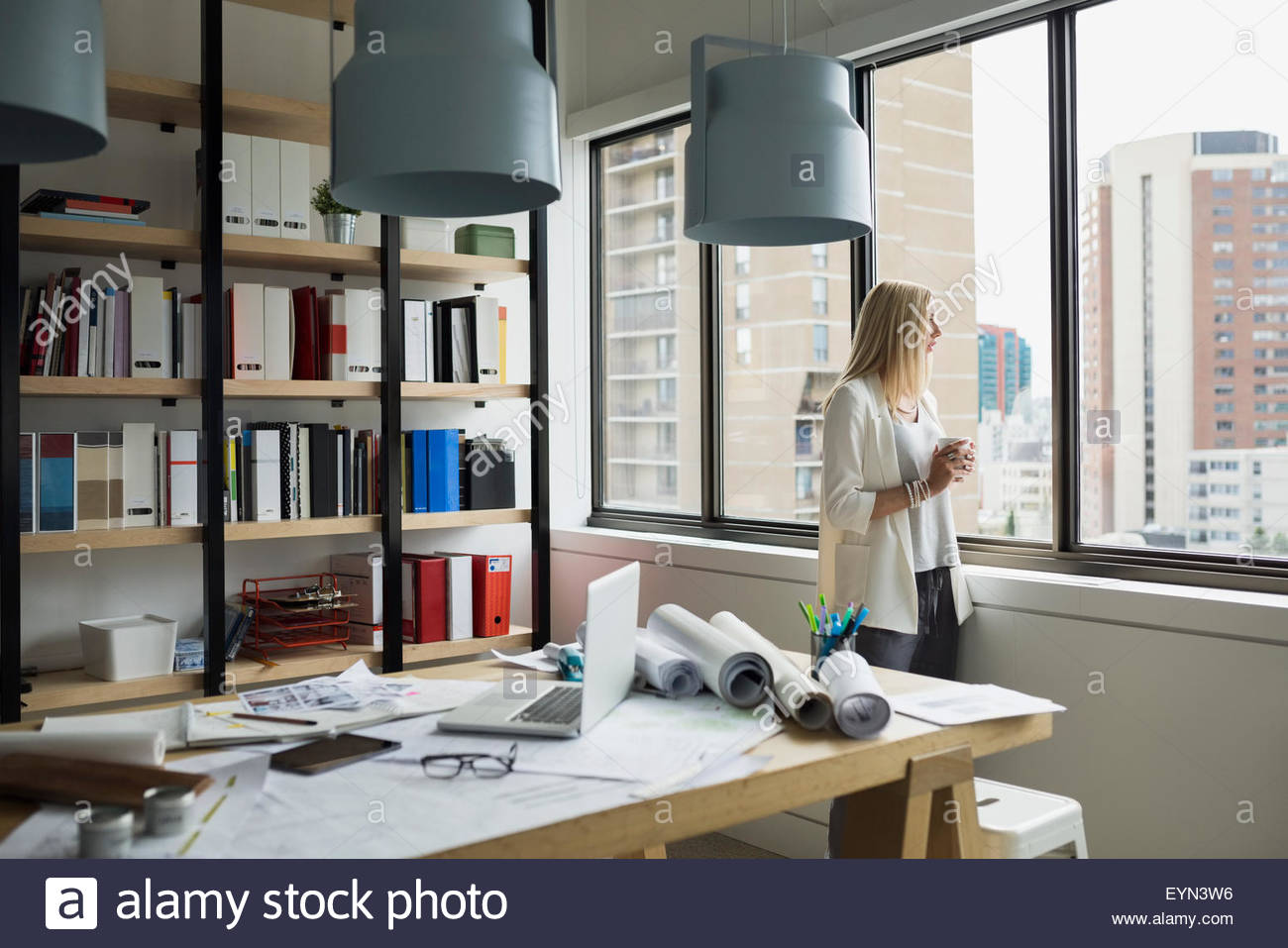 Pensive architect drinking coffee looking out office window - Stock Image