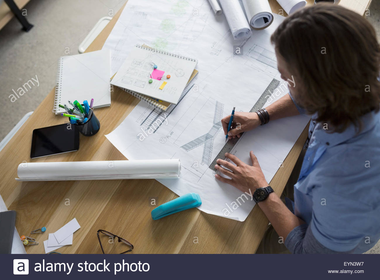 Overhead view of architect drafting blueprints at table - Stock Image
