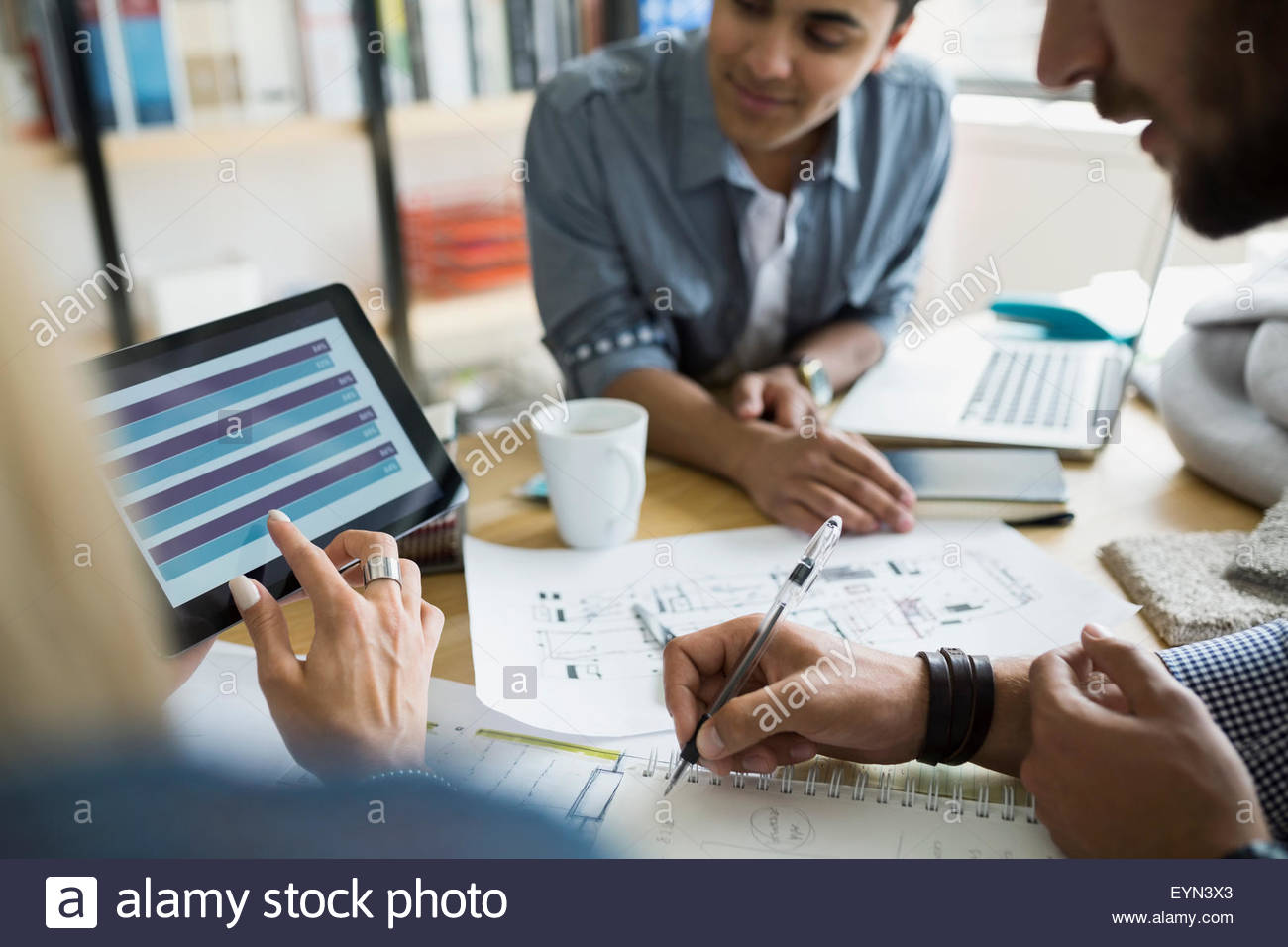 Architects with blueprints using digital tablet in meeting - Stock Image