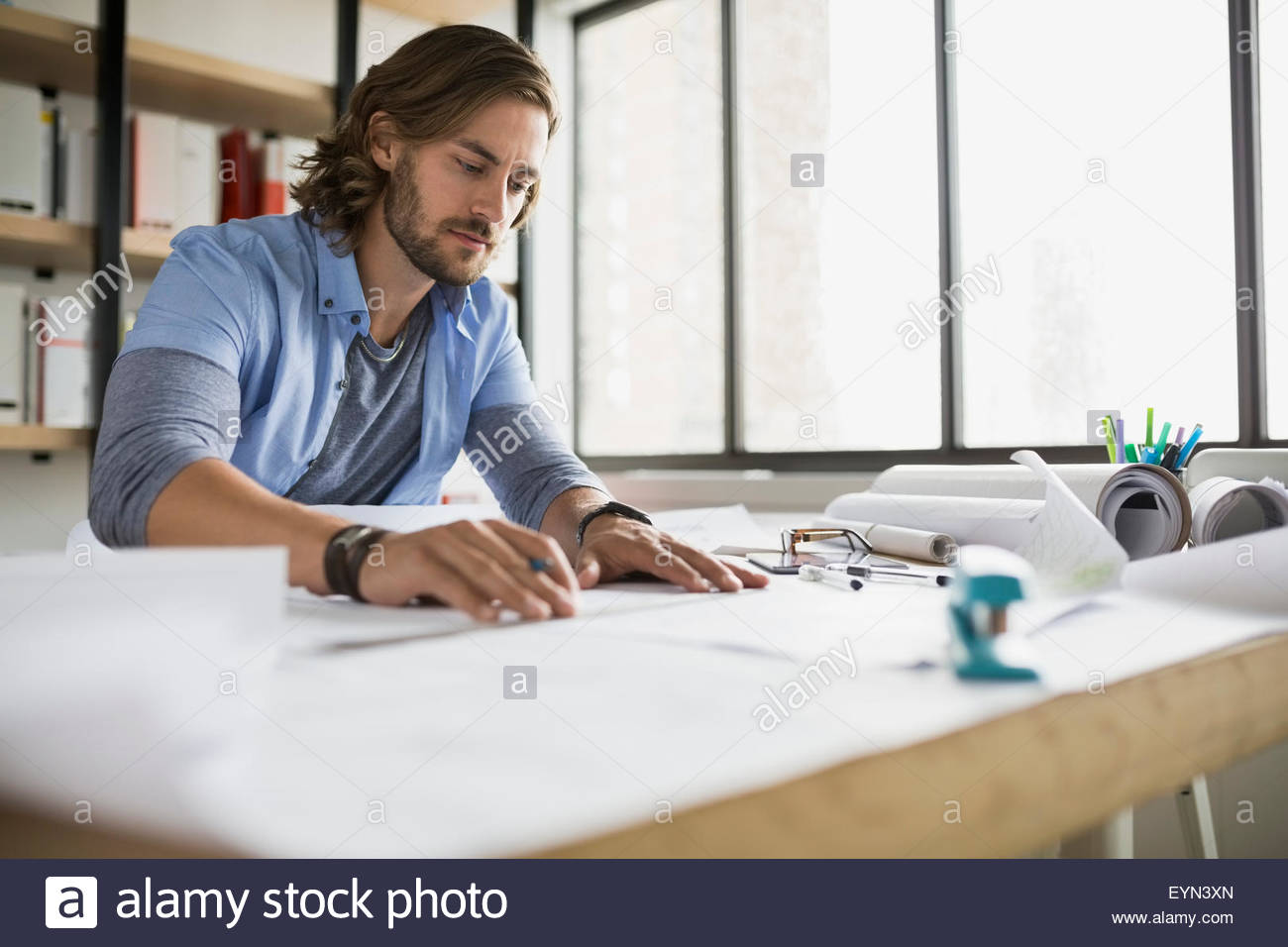 Architect drafting blueprints at table - Stock Image
