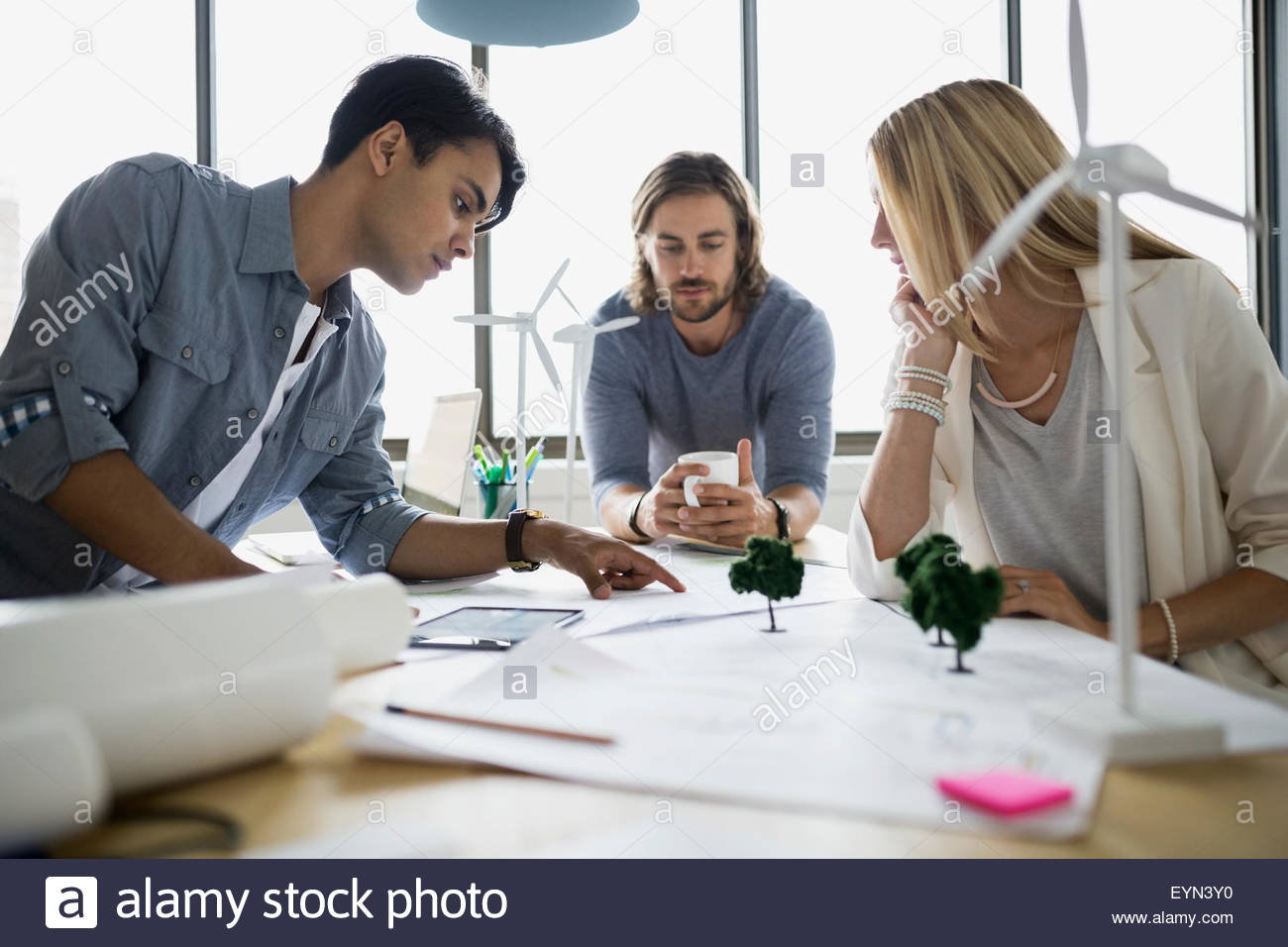 Architects discussing blueprints in meeting - Stock Image
