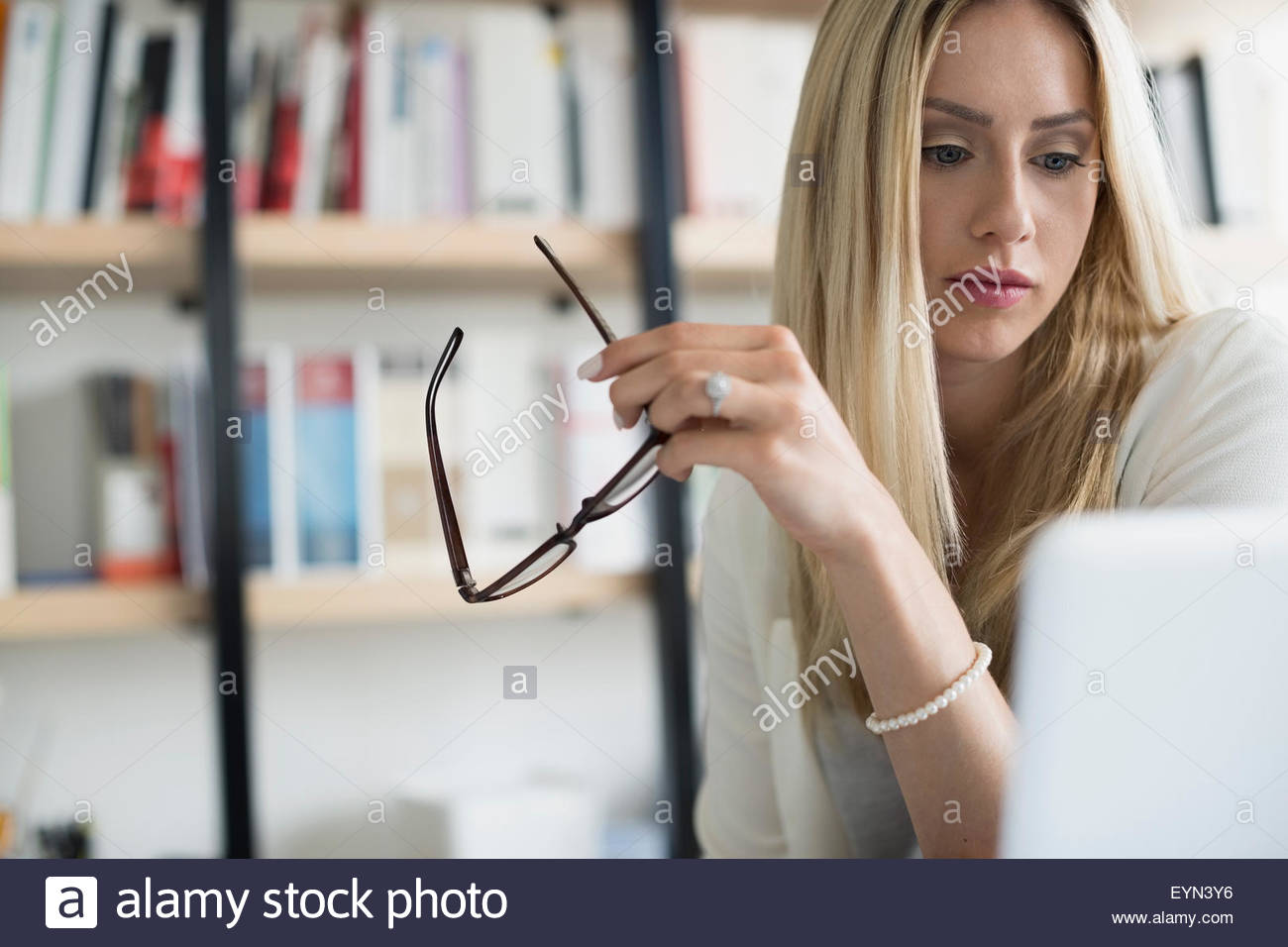 Serious businesswoman holding eyeglasses using laptop - Stock Image