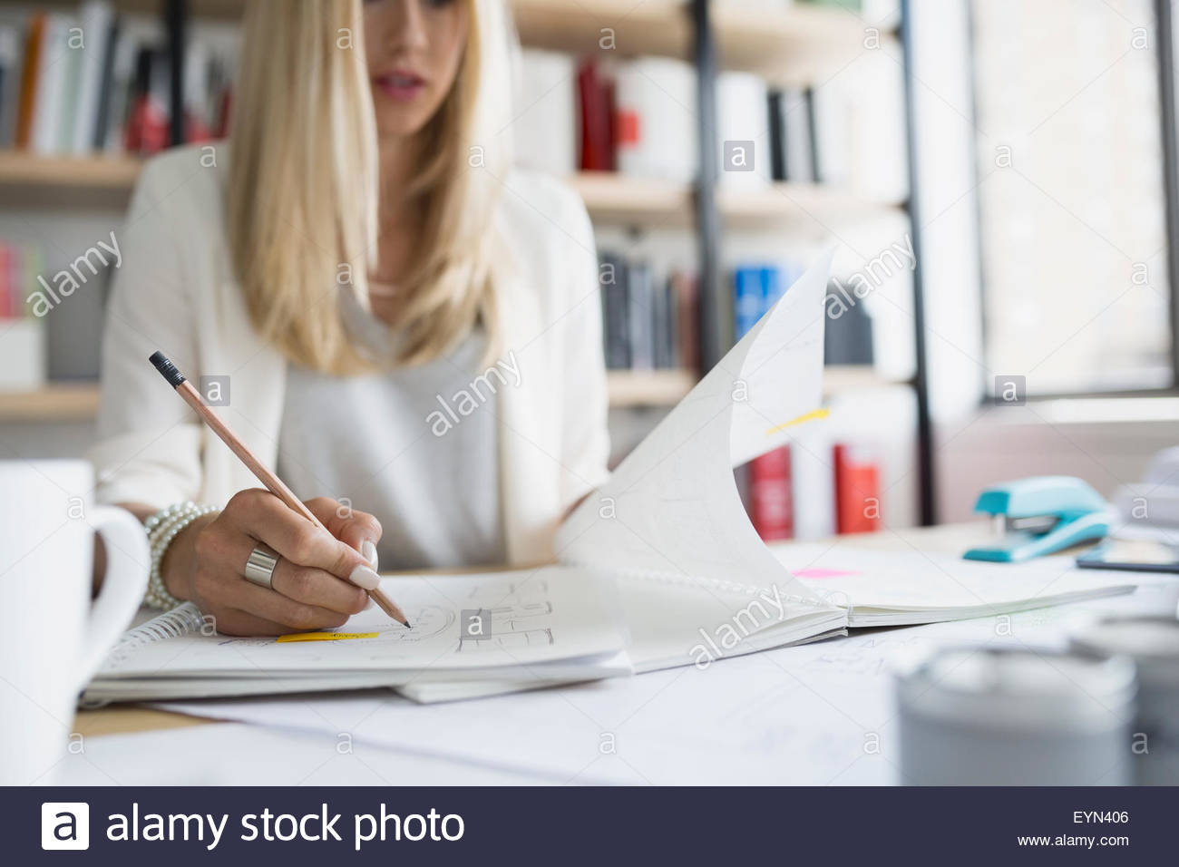 Architect drafting blueprints in office - Stock Image