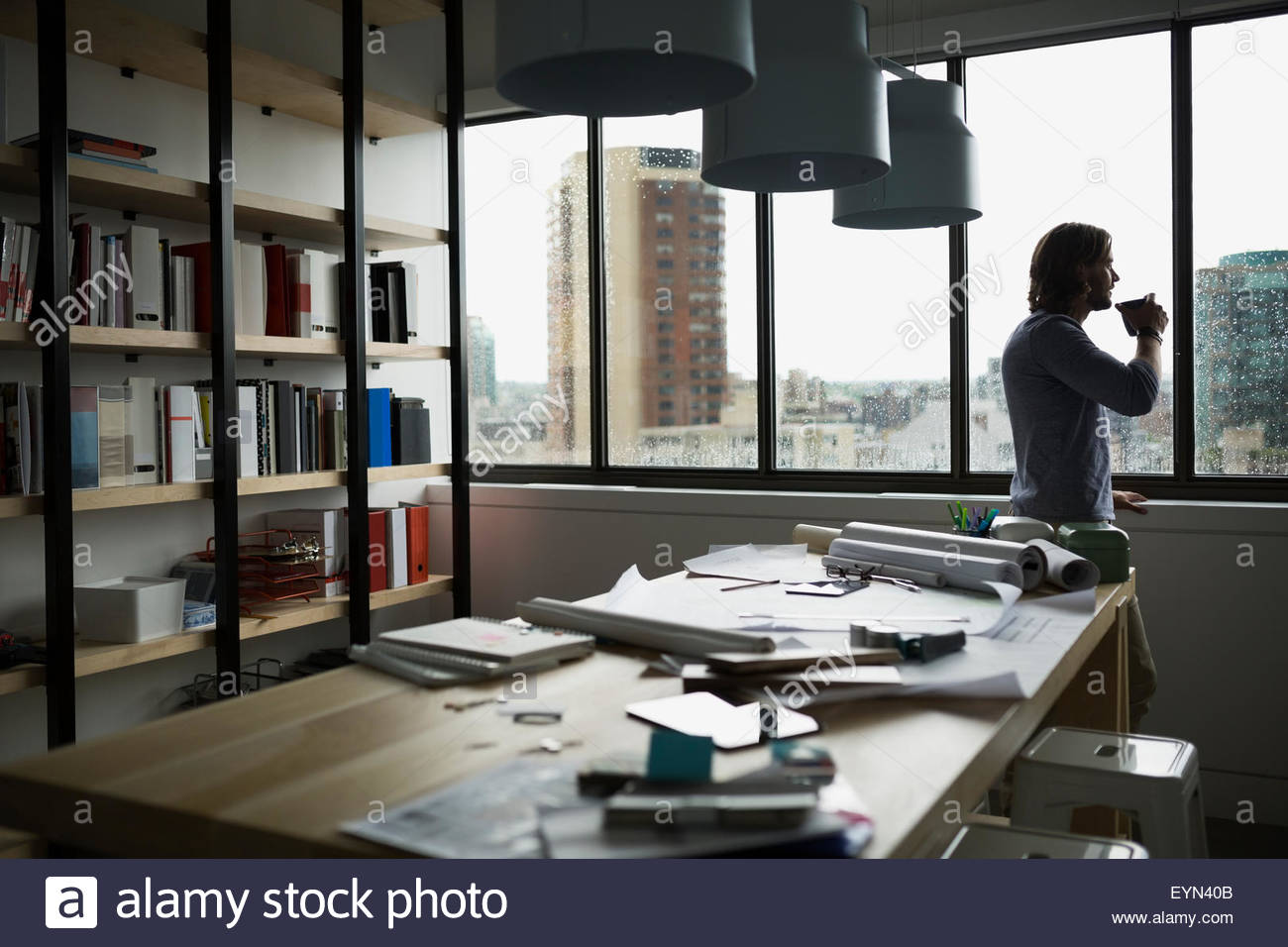 Architect drinking coffee at rainy office window - Stock Image