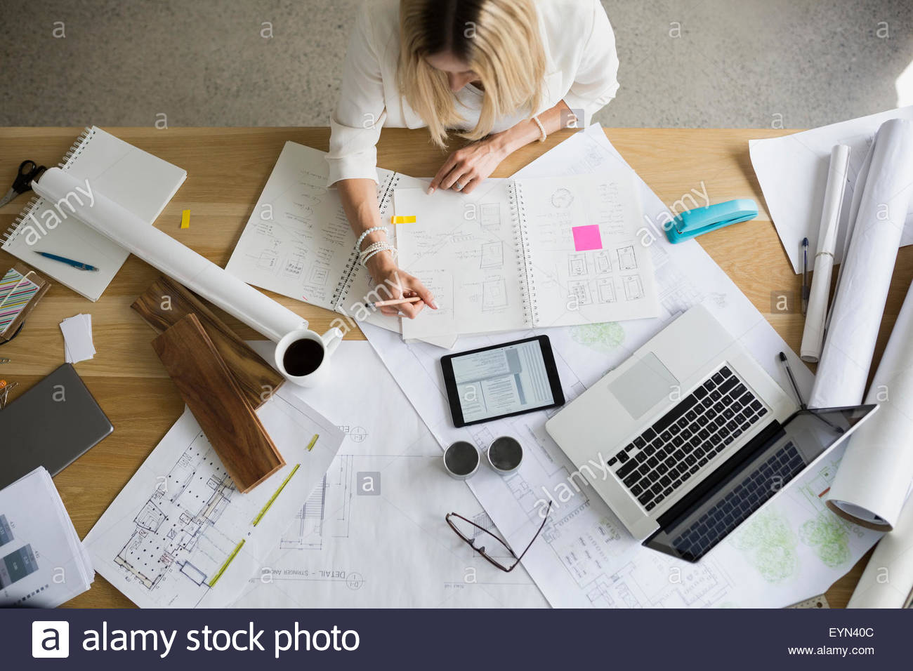 Overhead view architect drafting blueprints at table - Stock Image