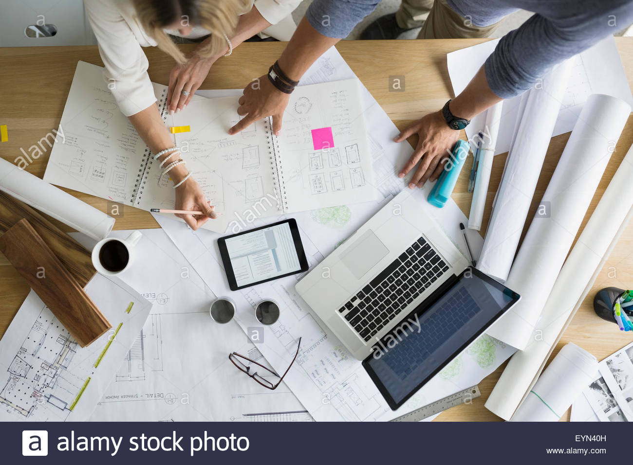 Overhead view architects drafting blueprints at table - Stock Image