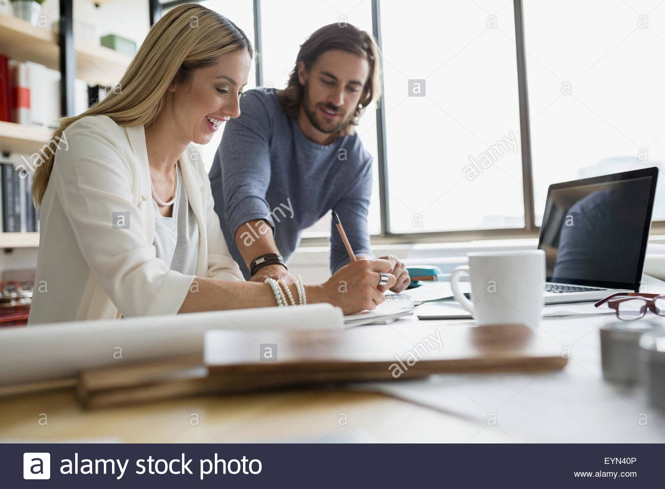 Architects drafting blueprints at table - Stock Image