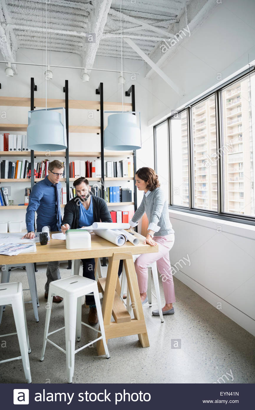 Architects meeting and reviewing blueprints in office - Stock Image