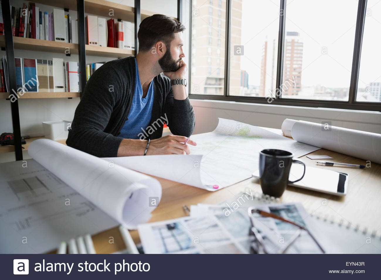 Pensive architect with blueprints looking away in office - Stock Image