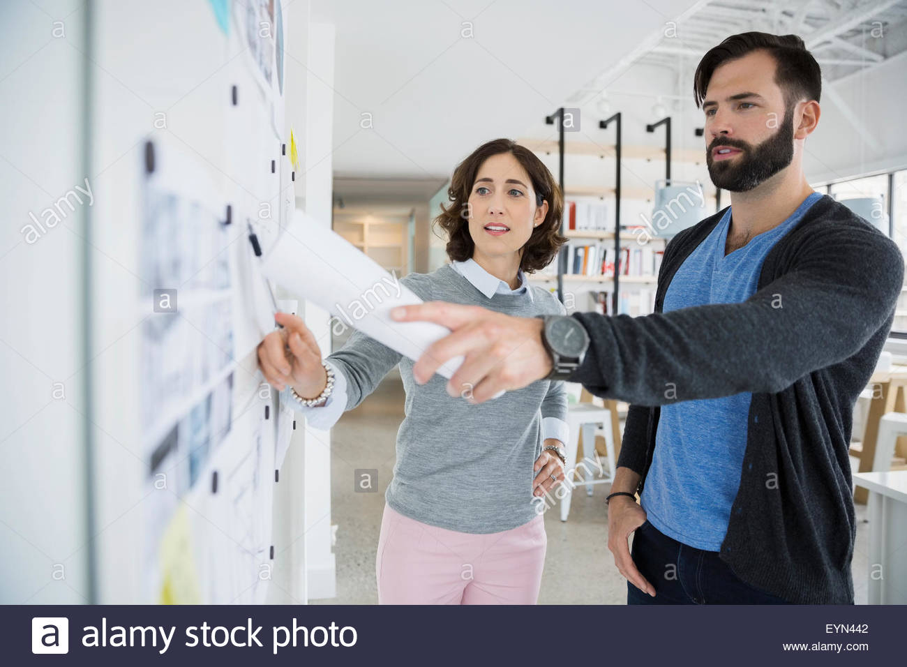 Architects meeting and discussing blueprints in office - Stock Image