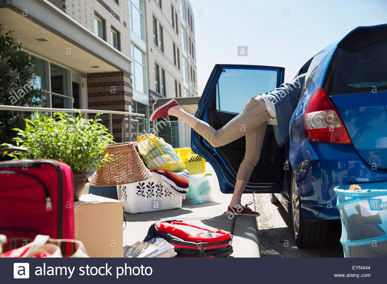 College student reaching in car moving into dorm - Stock Image