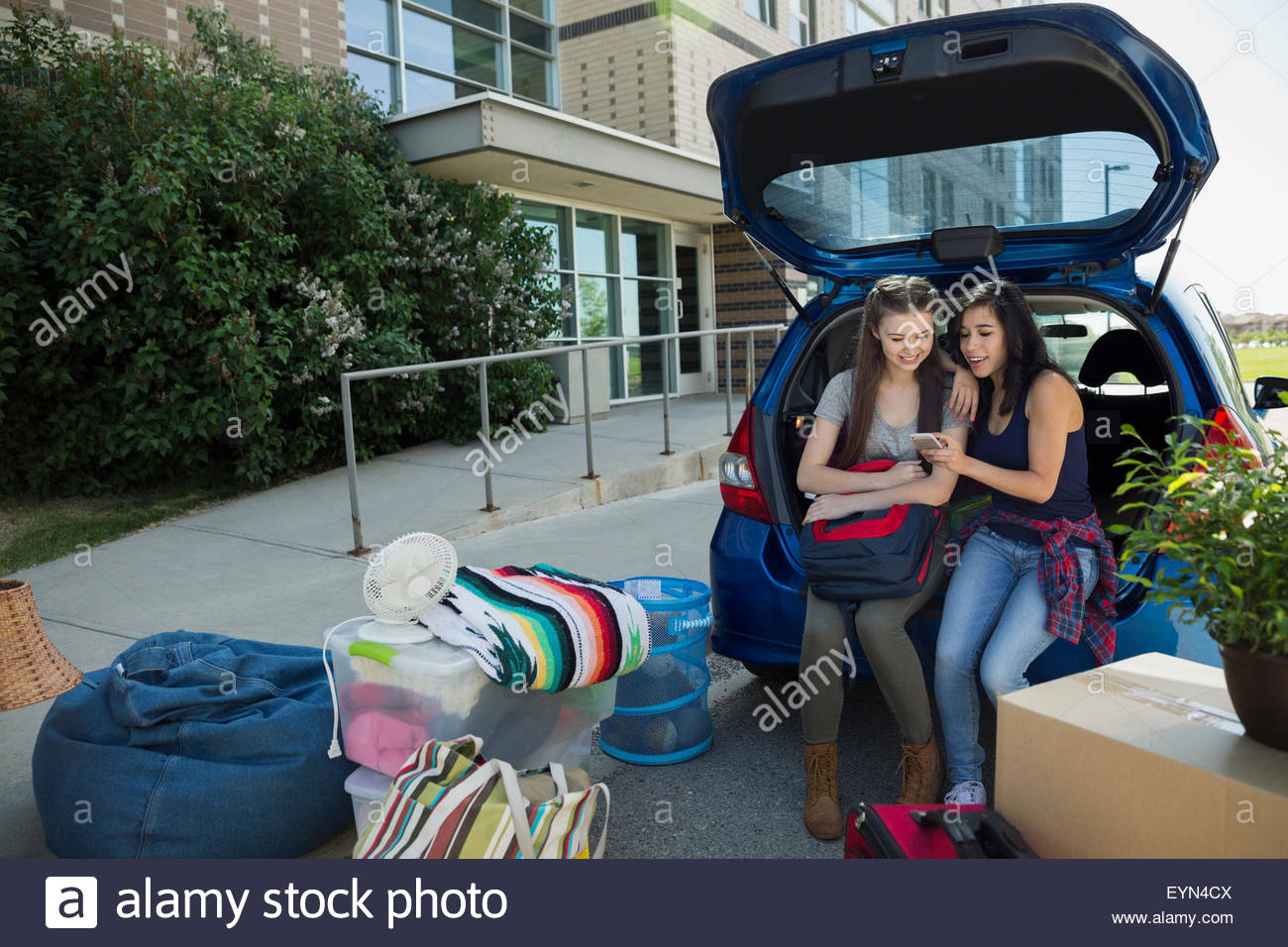 College students texting moving into college dorm - Stock Image