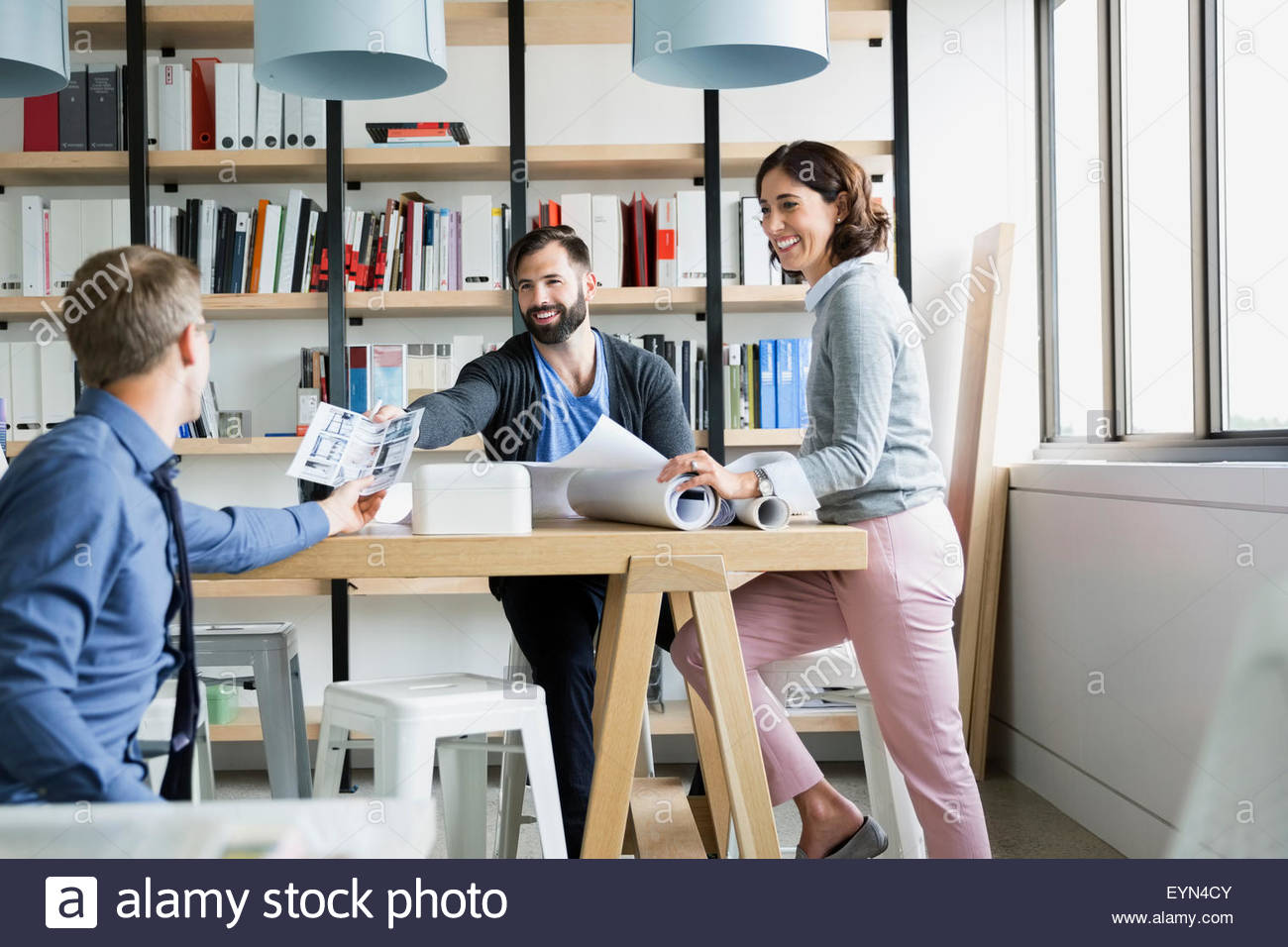 Architects reviewing proofs and blueprints in office - Stock Image