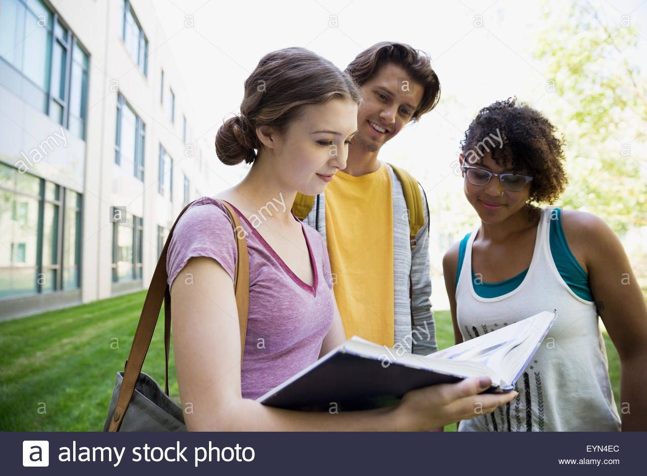 College students reading textbook on campus - Stock Image