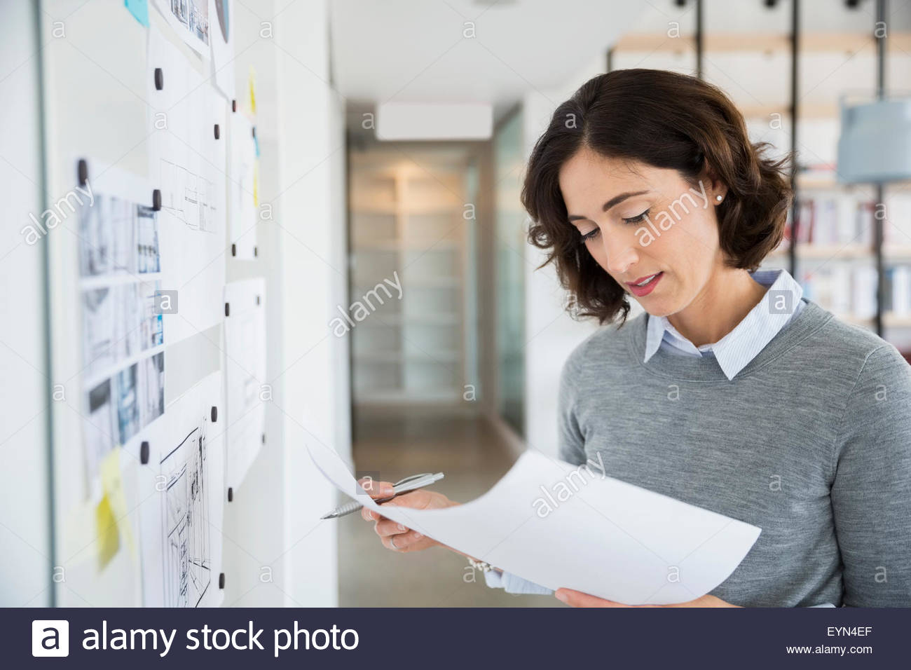 Architect reviewing blueprints at whiteboard in office - Stock Image
