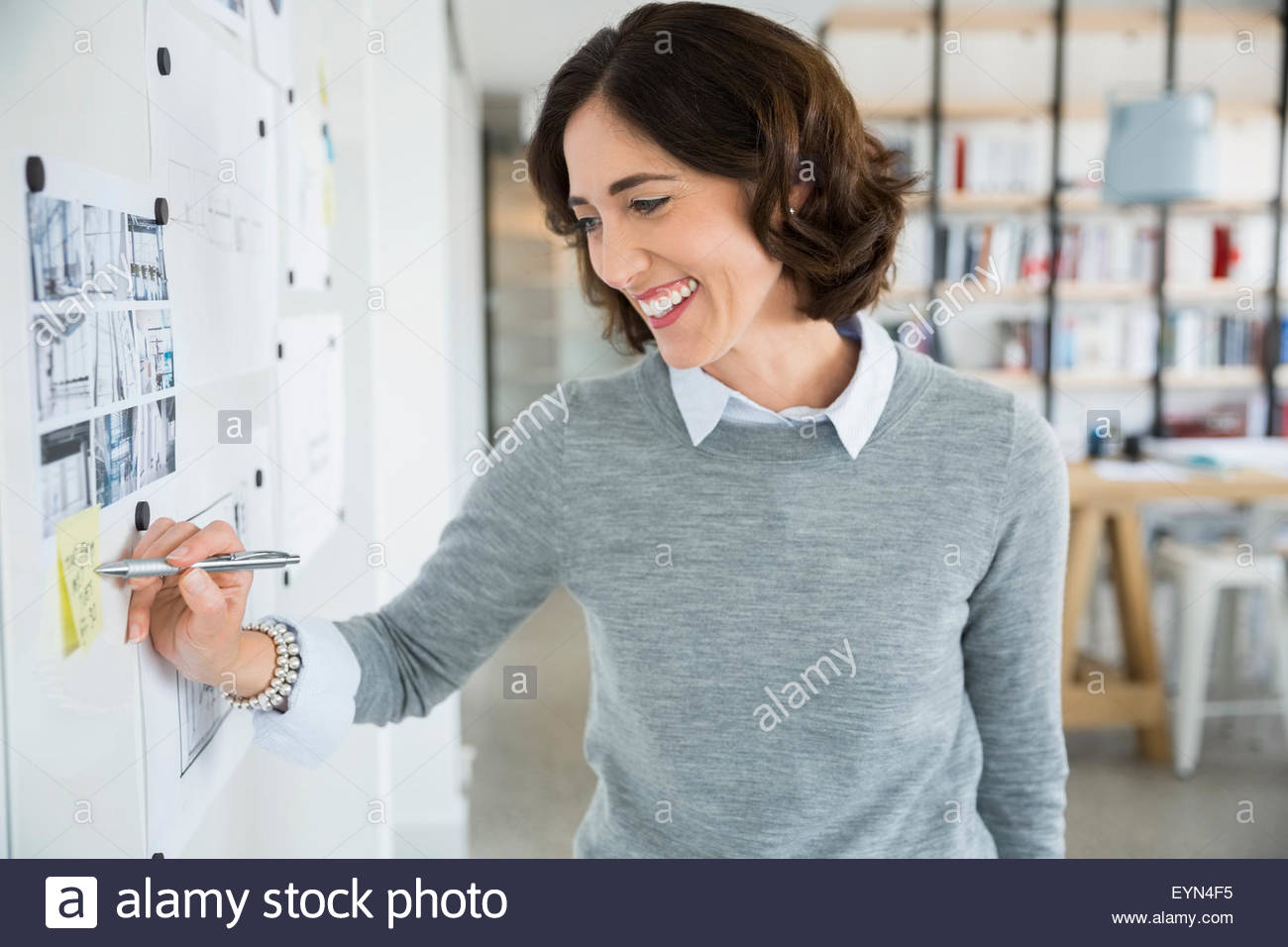 Smiling architect writing on adhesive note on wall - Stock Image