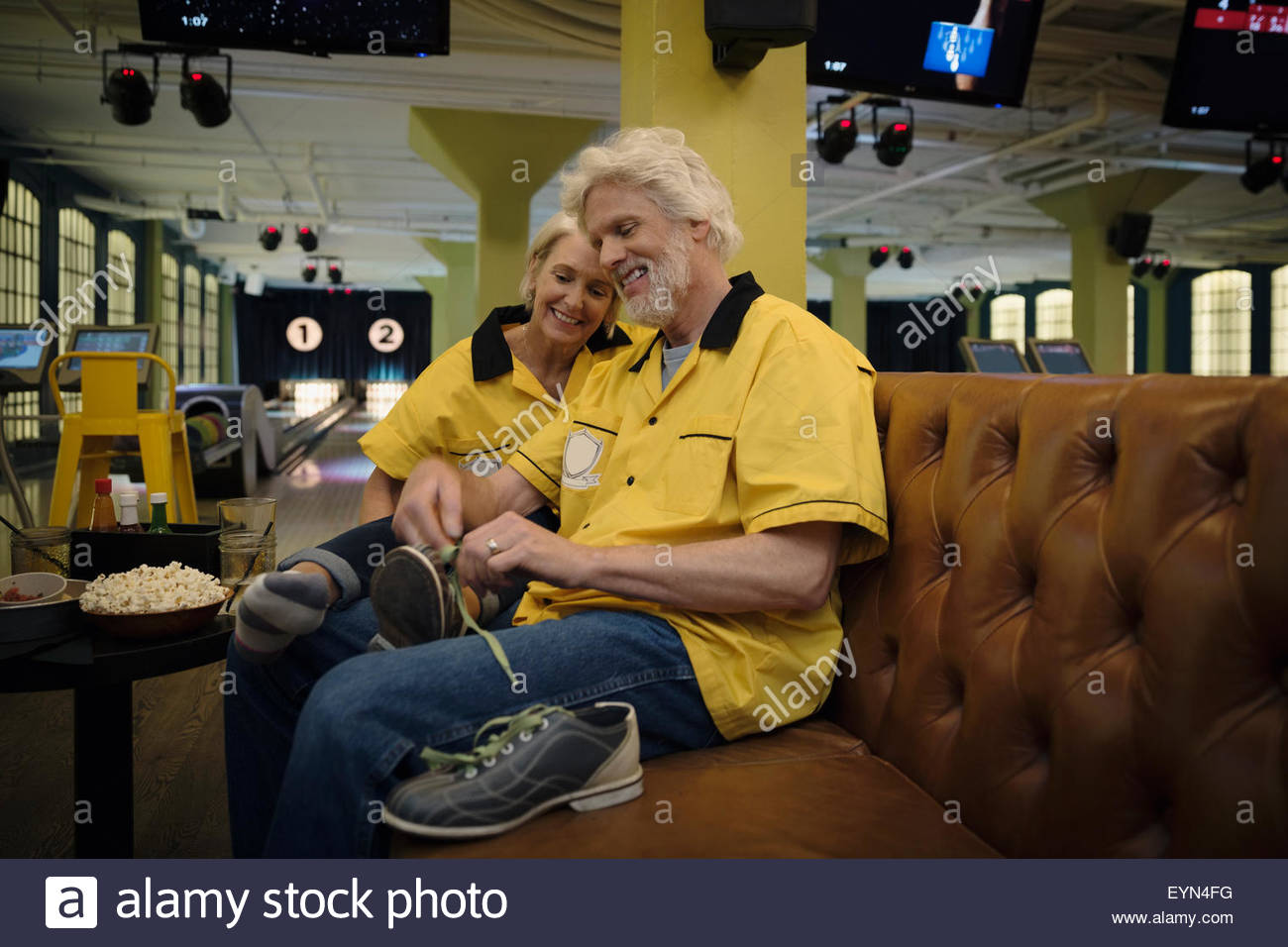 Husband untying wife bowling shoes in bowling alley - Stock Image