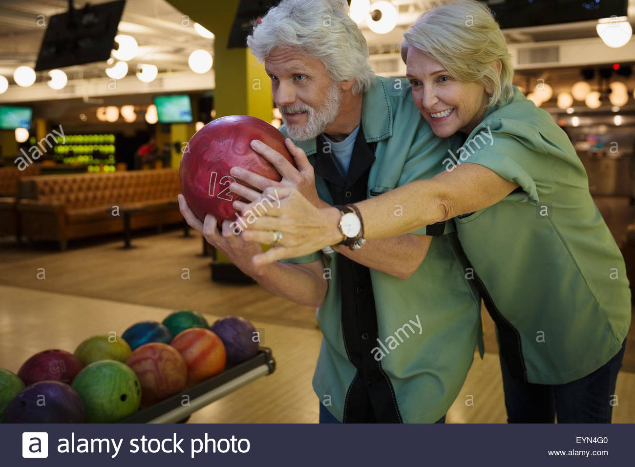 Wife guiding husband bowling at bowling alley - Stock Image