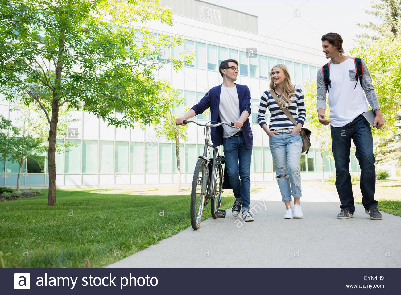 College students with bicycle walking on campus sidewalk - Stock Image